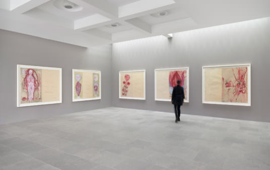 A blurred figure walks in a gray gallery space with a stone floor towards five large painted works on paper.
