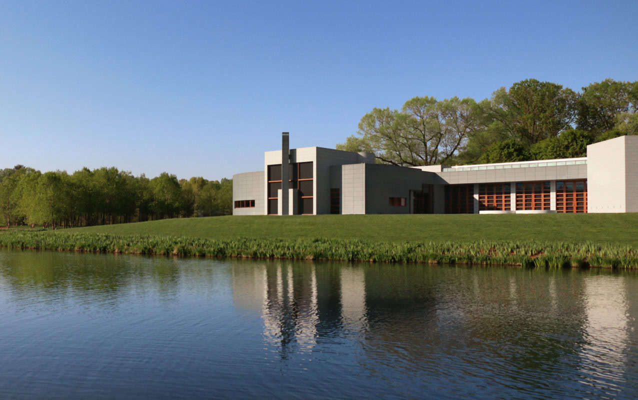 A gray building with a block design and wooden accents sits on a green lawn with a pond in the foreground.