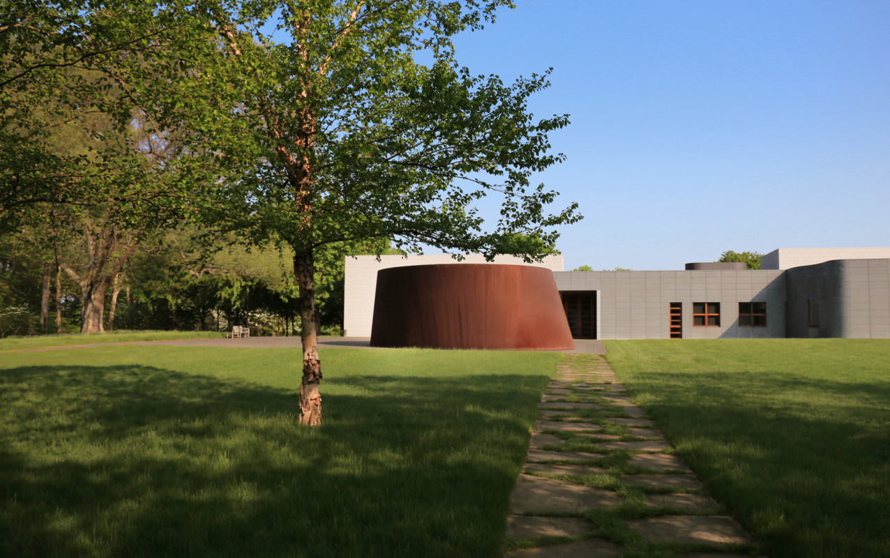A path runs through a lawn, leading to large weathering steel sculpture in front of a low gray building with a block design and wooden accents.
