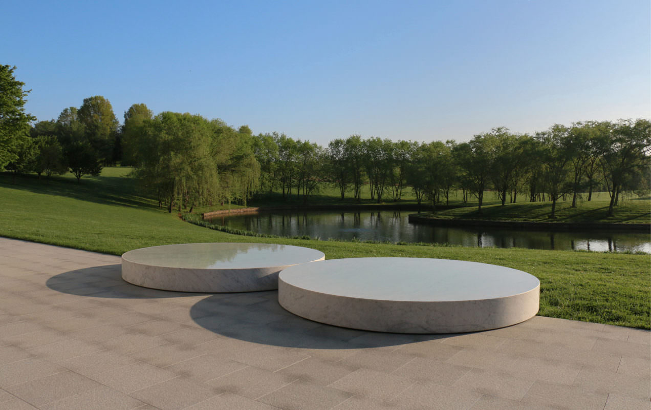 Two concave marble disks full of water sit across the border of a stone patio and a lawn, with a pond and willow trees in the background.