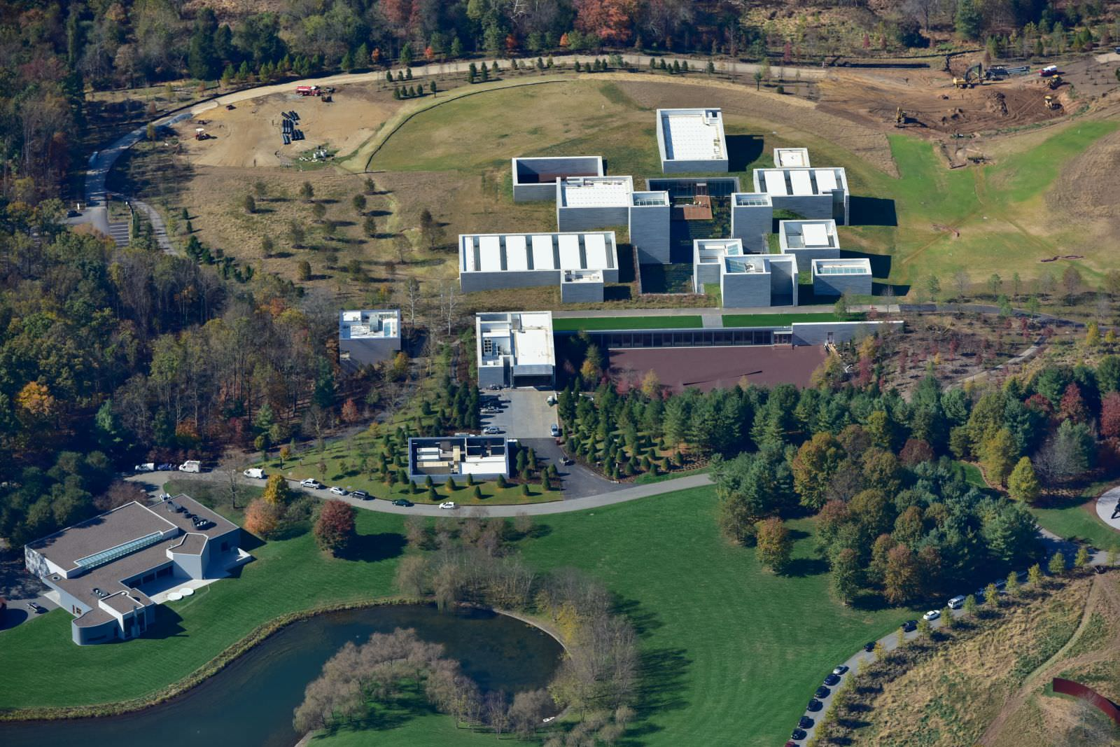 Rectangular gray buildings are surrounded by green trees, grass, and pond, seen from an aerial view.