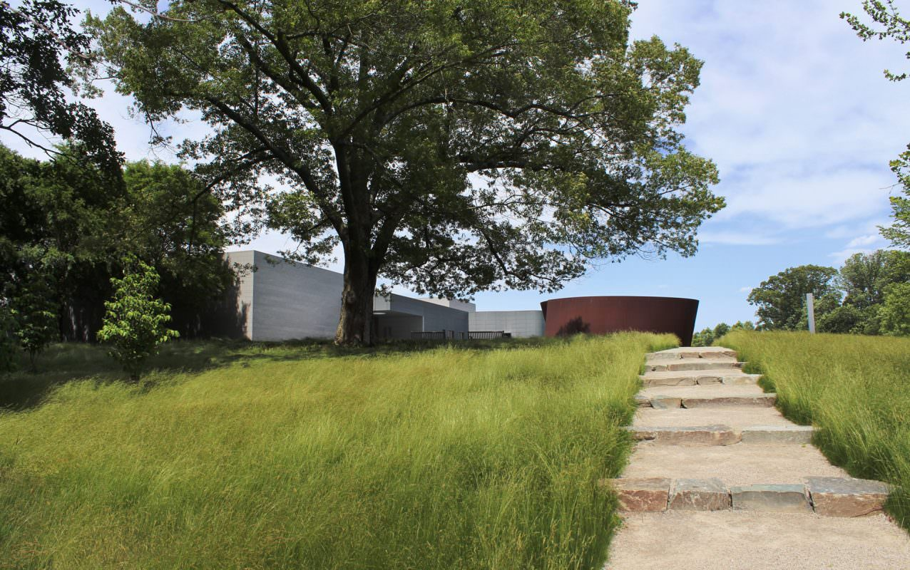 Six stone steps lead upwards through long grass towards a large metal sculpture, a large oak tree, and a building.