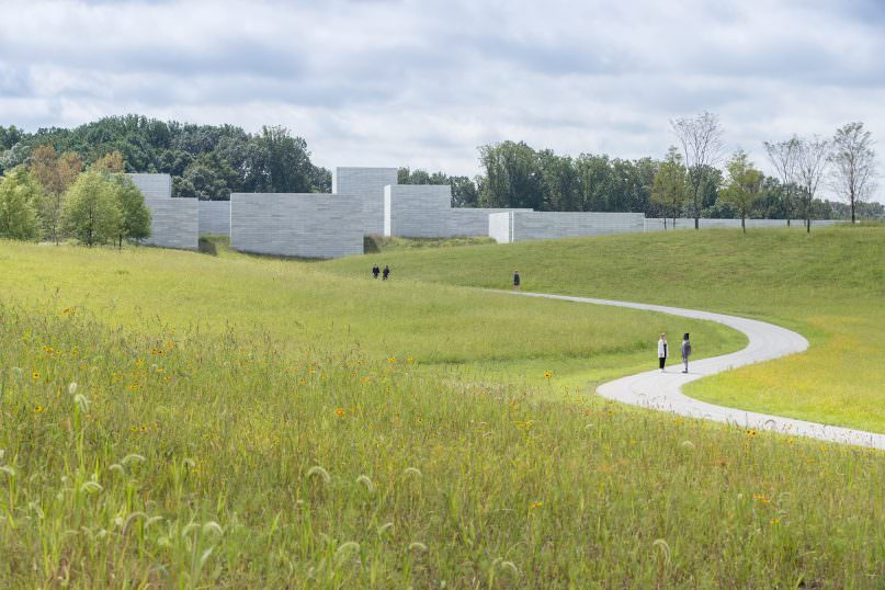 A gravel path cuts through an expanse of meadow. A number of visitors are moving toward the grey concrete buildings in the distance. Trees amass further in the landscape.