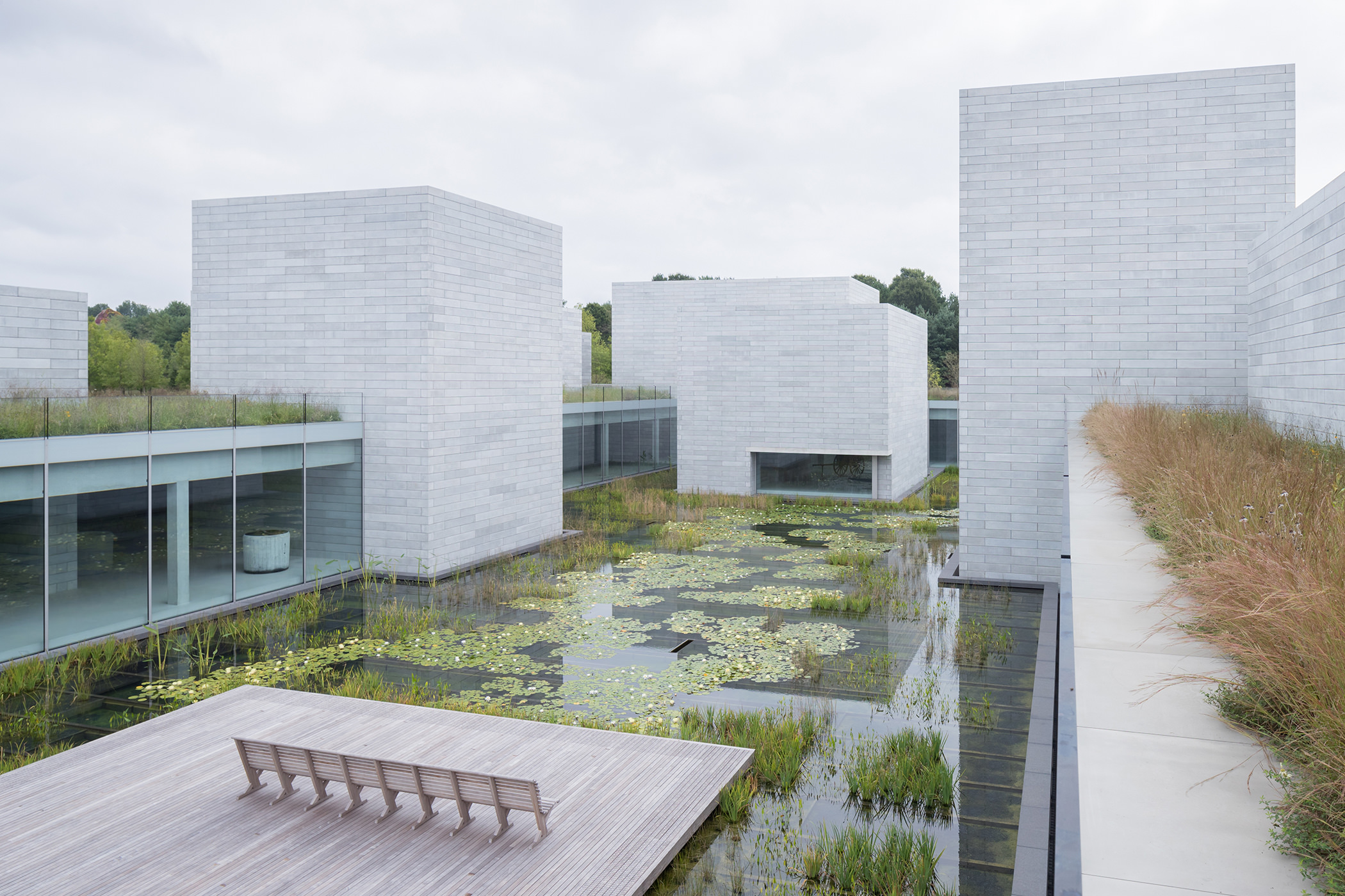 Gray concrete buildings surround a central water-count with a platform and a bench. The water court is full of plant life.
