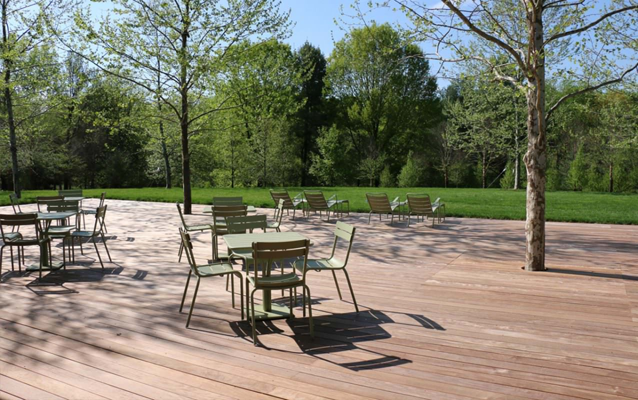Green tables and chairs sit on a low wooden platform in front of a green lawn, with a forest in the background.