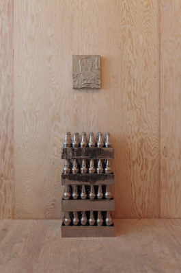 Four crates containing metallic beer bottles are stacked below a metallic portrait of Mao Zedong in a plywood room.